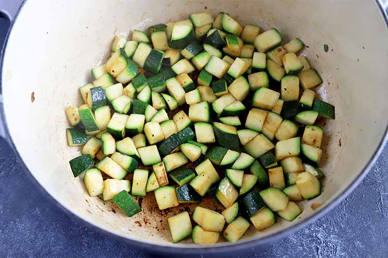 Horizontal image of diced zucchini in a pot.