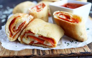 Horizontal image of four slices of pepperoni and cheese rolls on a baking sheet on a wooden cutting in front of marinara sauce.