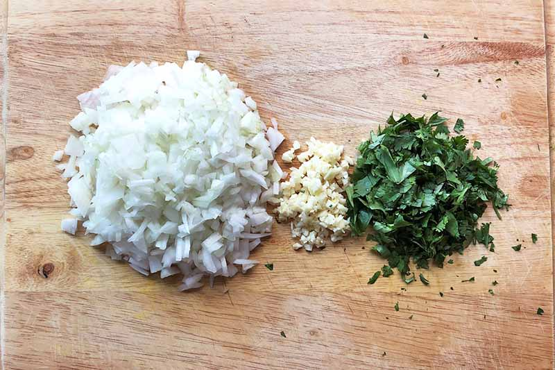 Horizontal image of a mound of diced onions, minced garlic, and chopped herbs.