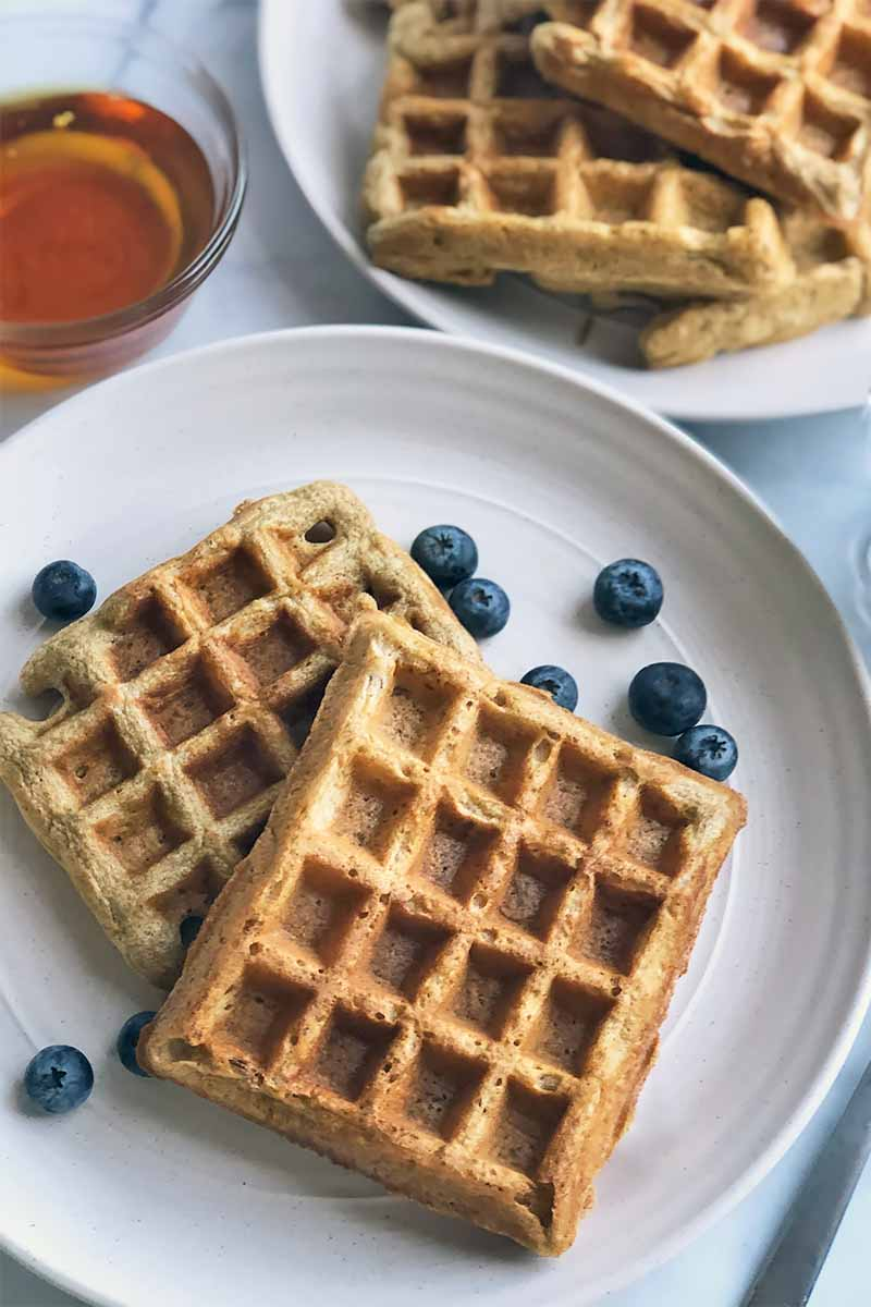 Vertical image of rectangular waffles on two white plates with fresh blueberries next to a small glass bowl of maple syrup.