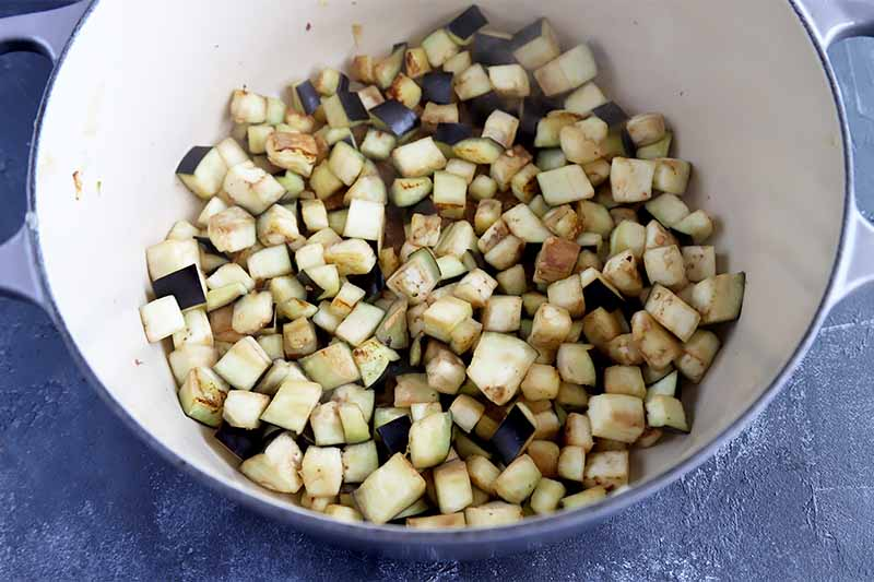 Horizontal image of cooking diced eggplant in a pot.