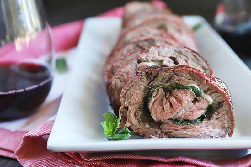Horizontal image of a white plate with slices of a rolled beef dish filled with basil and melted cheese next to a glass of wine.
