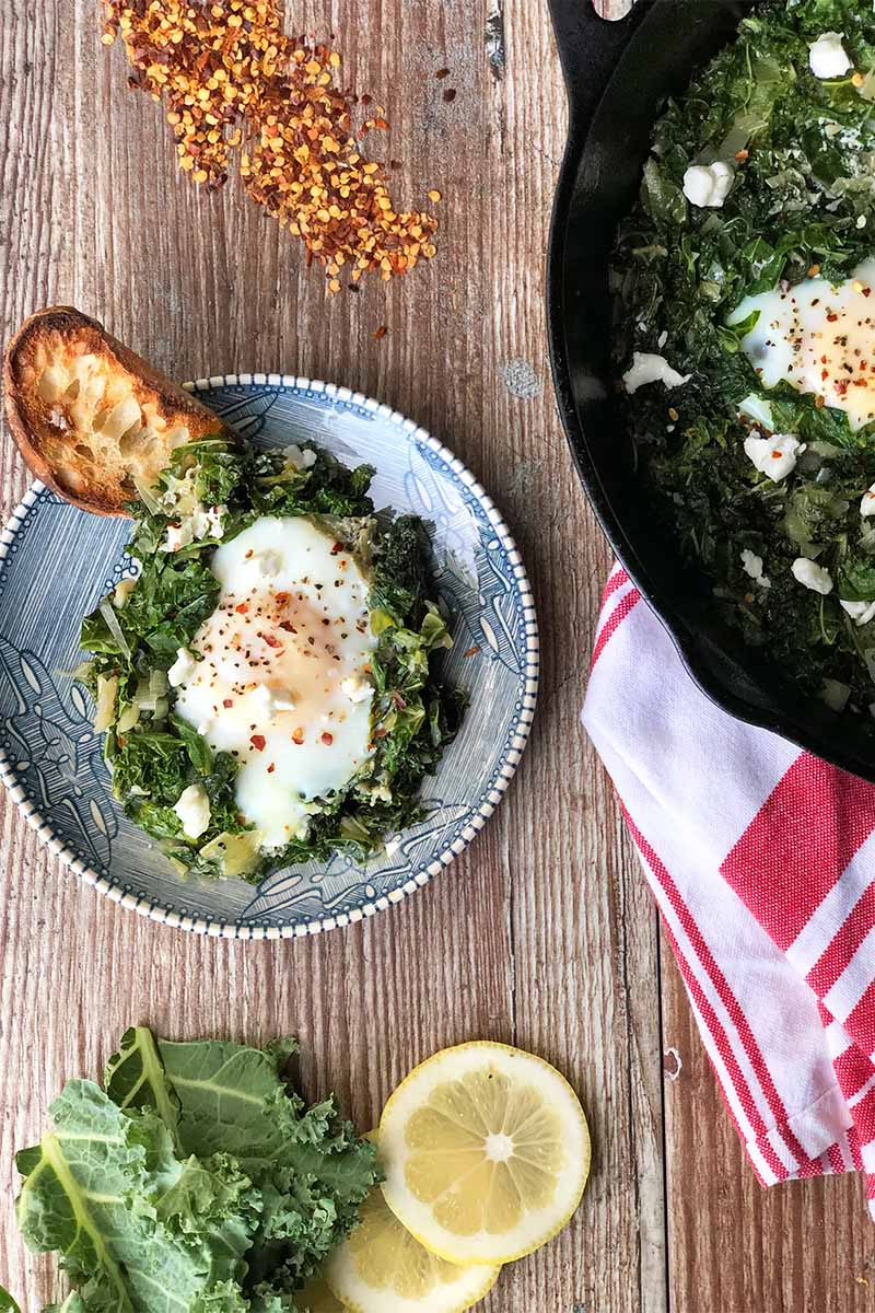 Vertical image of a plate and a skillet with greens and lightly cooked eggs with lightly toasted read next to a towel, lemon slices, and red pepper flakes.