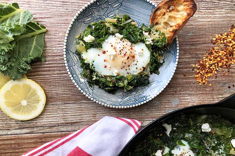 Horizontal image of a plate and a skillet with greens and lightly cooked eggs with lightly toasted read next to a towel, lemon slices, and red pepper flakes.