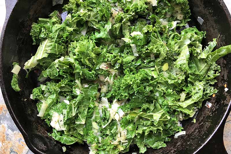 Horizontal image of cooking kale with aromatics in a cast iron skillet.