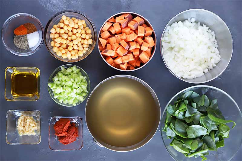 Horizontal image of assorted prepped veggies, broth, and seasonings on a dark surface.