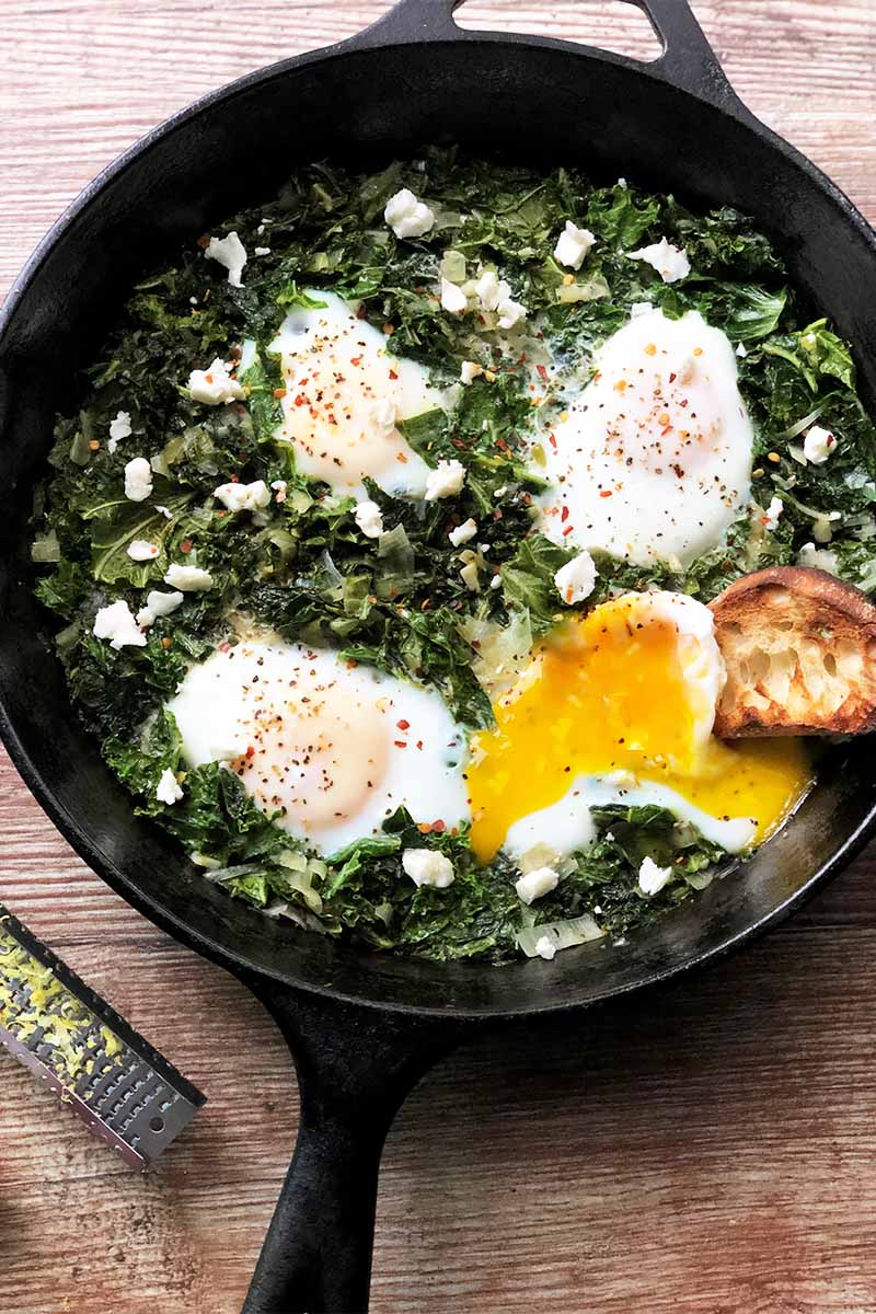 Vertical image of a cast iron skillet with greens and four lightly cooked eggs on a wooden table.