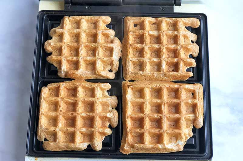 Horizontal image of four cooked Belgian waffles in a cooking iron.