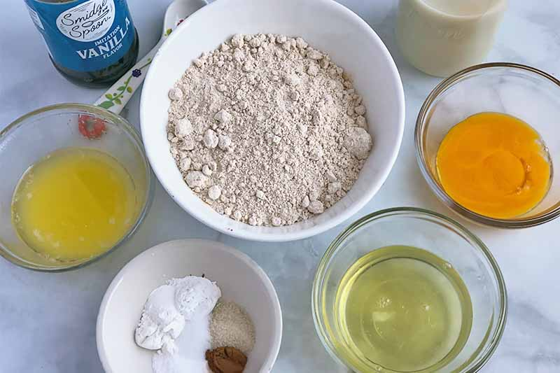 Horizontal image of bowls of melted butter, dry seasonings, flour, egg whites, egg yolks, and a bottle of vanilla extract.