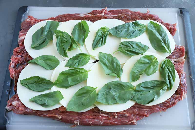 Horizontal image of whole basil leaves on top of shingled slices of provolone on top of a thin slab of raw beef on a cutting board.