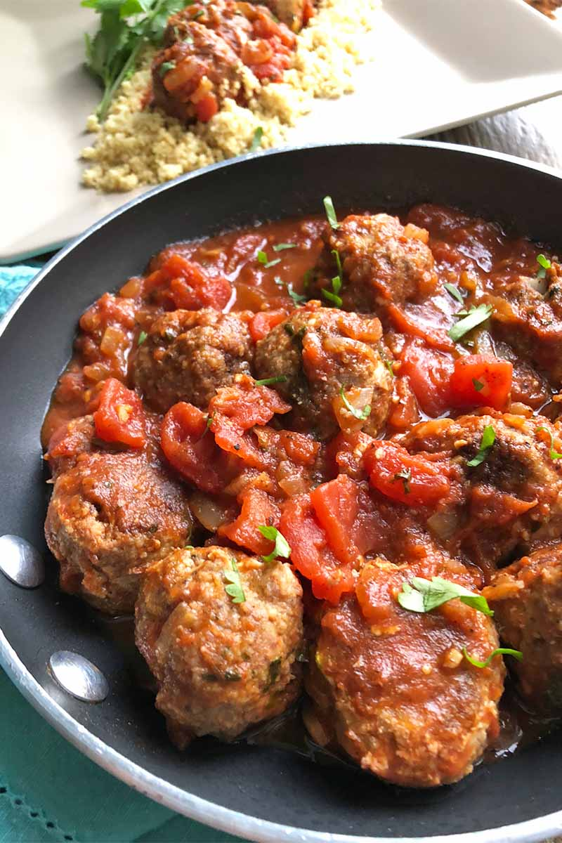 Vertical image of a black pan filled with small mounds of cooked ground lamb covered in a tomato sauce.