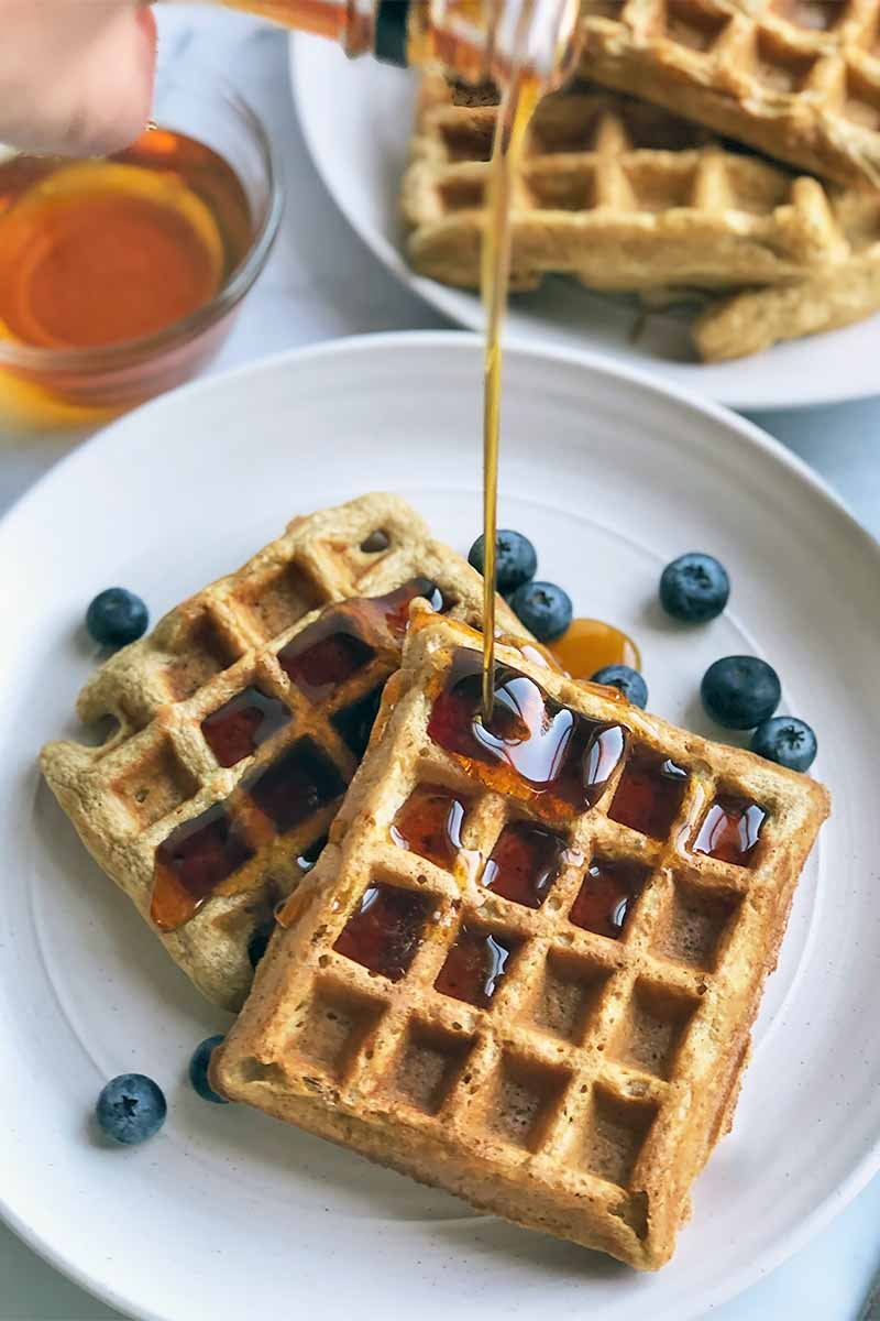 Vertical image of pouring maple syrup over a plate of rectangular waffles scattered with blueberries, with more waffles in the back on a white plate.