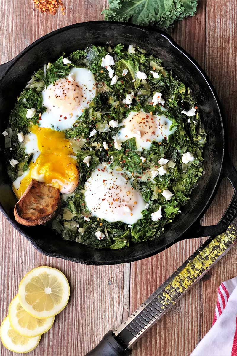 Vertical top-down image of a cast iron skillet with cooked greens and whole eggs with crumbled goat cheese on top next to lemon slices and a zester.