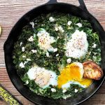 Horizontal image of a cast iron skillet filled with cooked greens and lightly cooked eggs next to lemon slices, red pepper flakes, and a zester.