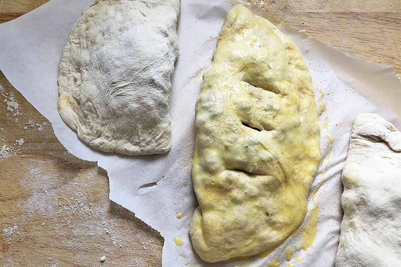 Horizontal image of three unbaked calzones washed with egg on a piece of parchment paper.