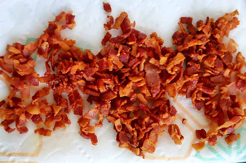Horizontal image of cooked bacon bits on a paper towel.