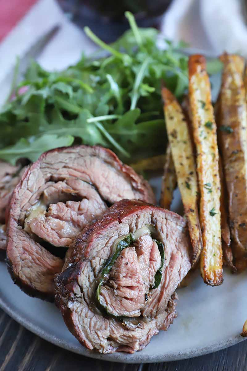 Vertical close-up image of two rolled beef medallions filled with basil and cheese on a white plate next to arugula and seasoned fries.