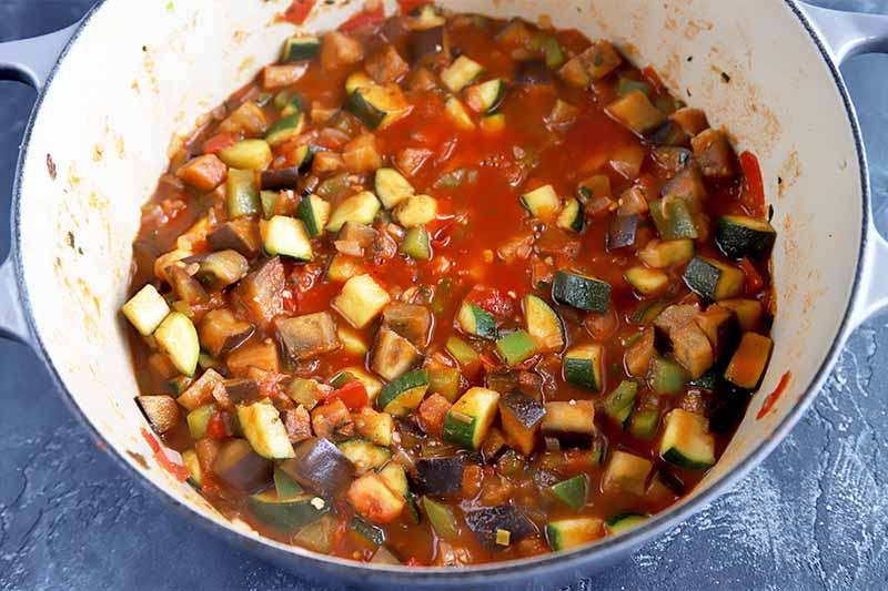 Horizontal image of assorted diced vegetables cooking in a tomato sauce in a pot.