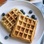 Horizontal image of rectangular waffles on two white plates with fresh blueberries next to a small glass bowl of maple syrup and a bowl of blueberries and a metal fork.
