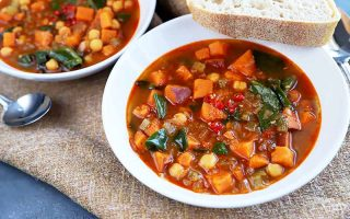 Horizontal image of two white bowls filled with a hearty vegetable stew on a burlap towel with a slice of bread and a metal spoon.
