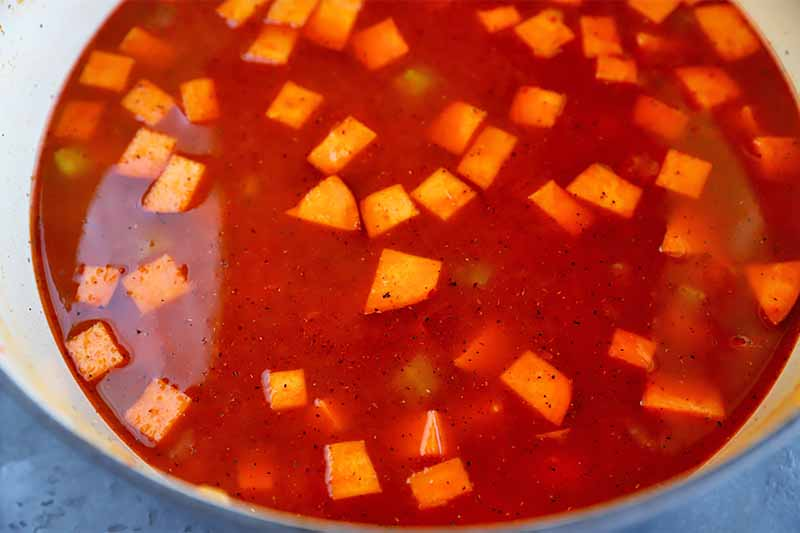 Horizontal image of sweet potato cubes in a red stew in a pot.
