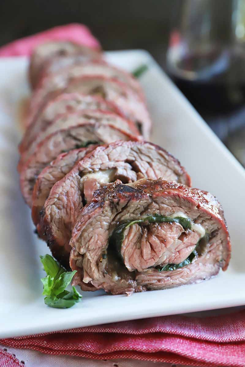 Vertical image of a white plate with slices of a rolled beef dish filled with basil and melted cheese.