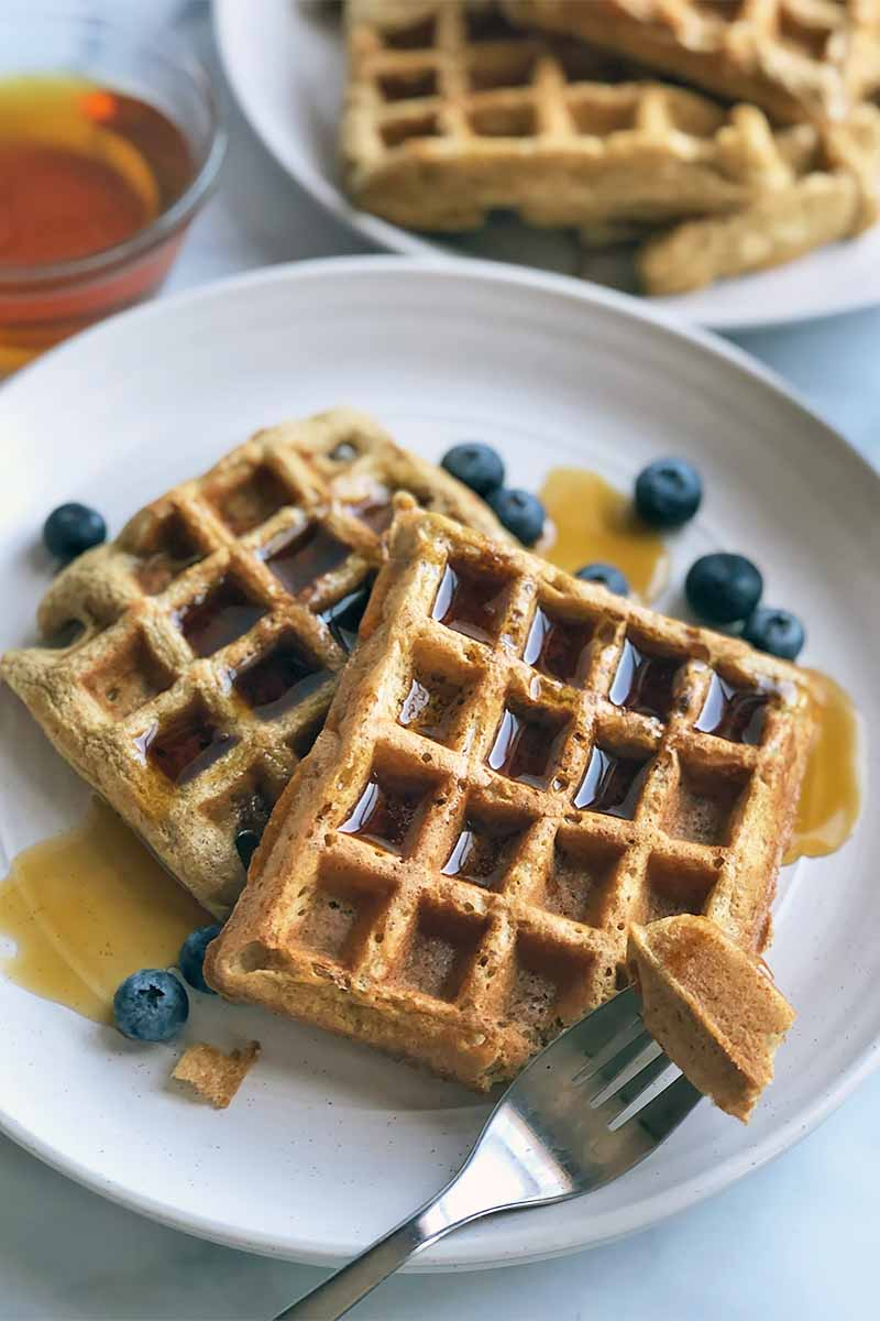 Vertical image of a fork taking a piece out of Belgian waffles on a white plate with maple syrup and blueberries.