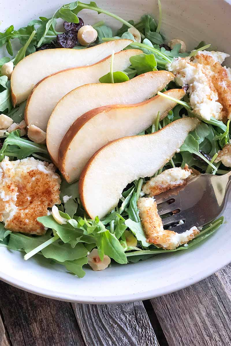 Vertical close-up image of shingled pears over a bed of arugula with fried goat cheese balls.