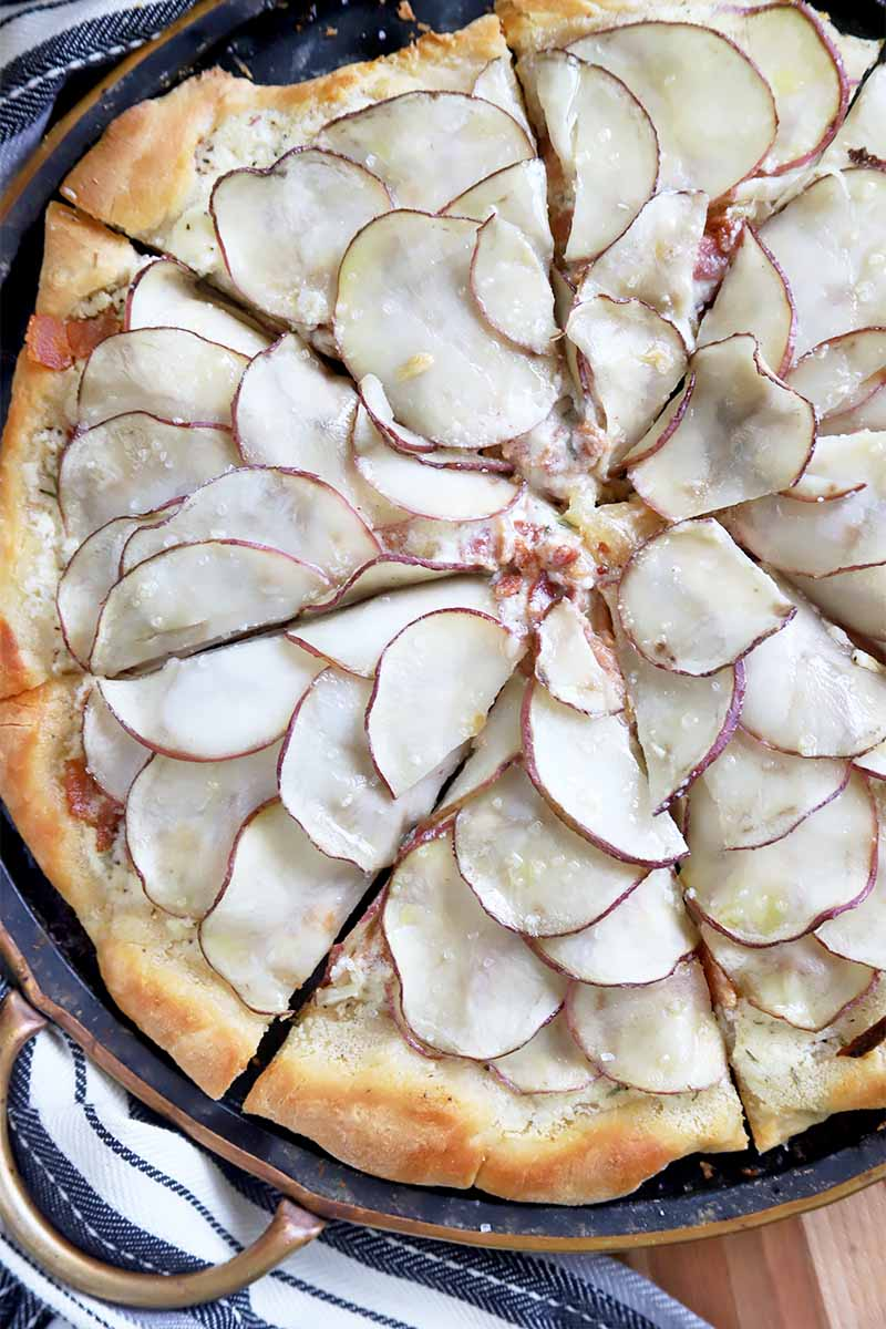 Vertical top-down image of a sliced whole pizza covered in thinly sliced white vegetables that are neatly shingled.