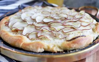 Horizontal image of a whole pizza topped with shingled thinly sliced potatoes.