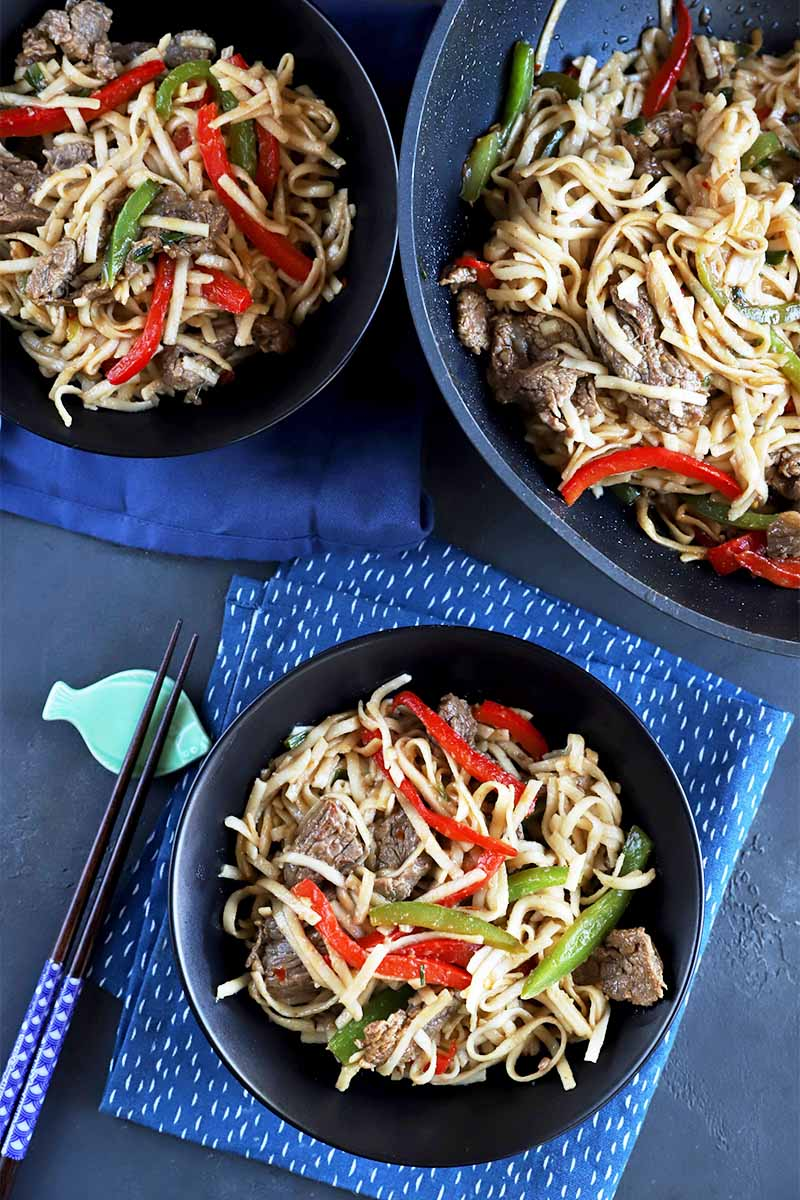 Vertical image of bowls and a pan with a steak, noodle, and bell pepper dish on blue towels next to chopsticks.