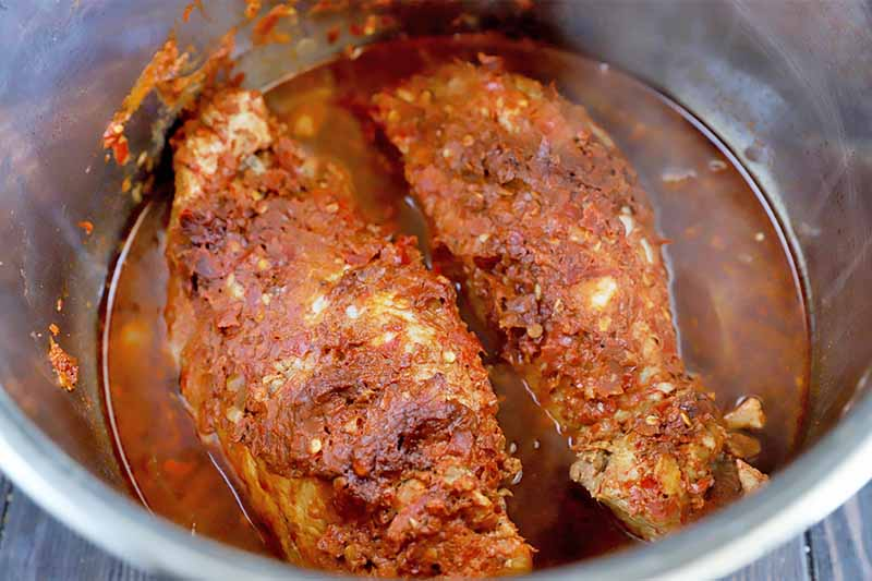 Horizontal image of a bowl of cooked meat covered in a thick red seasoning with natural juices around it.