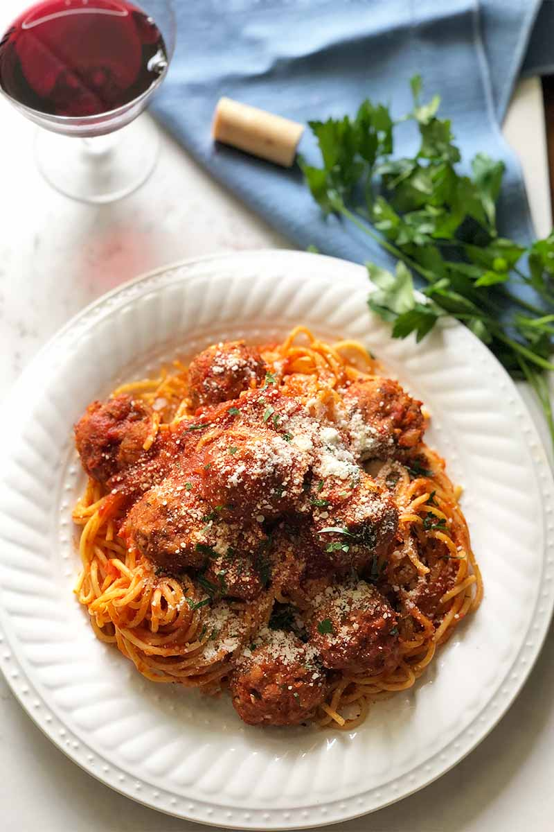 Vertical image of a large white plate filled with a pasta, marinara, and meatball dish next to fresh herbs and a blue towel and a glass of wine.