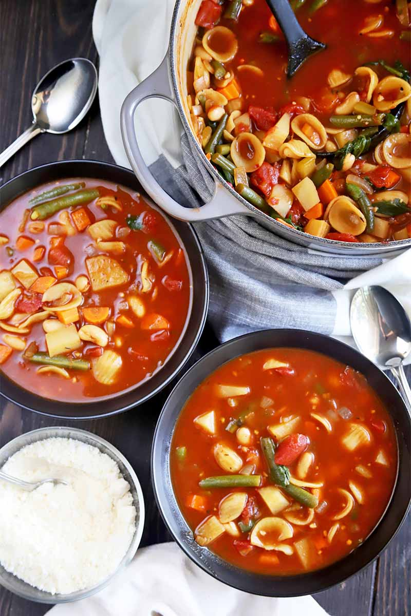 Vertical top-down image of two bowls and a large pot filled with a tomato, mixed vegetable, and pasta stew next to a white towel, metal spoons, and bowl of grated cheese.