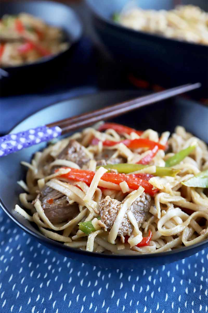 Vertical image of a black bowl filled with a meat, pepper, and noodle dish next to chopsticks on a blue towel.