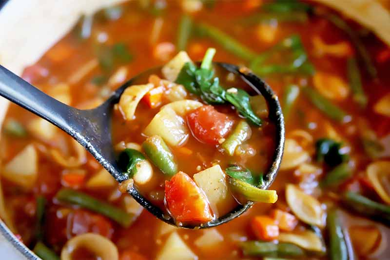 Horizontal image of a plastic ladle holding a large scoopful of an assorted vegetable stew in a pot.