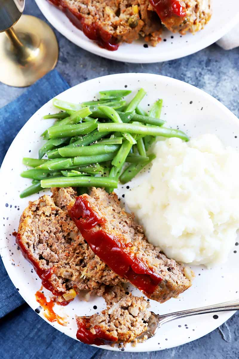 Vertical top-down image of a fork removing a large piece of a beef dish on a plate with mashed potatoes and green beans.