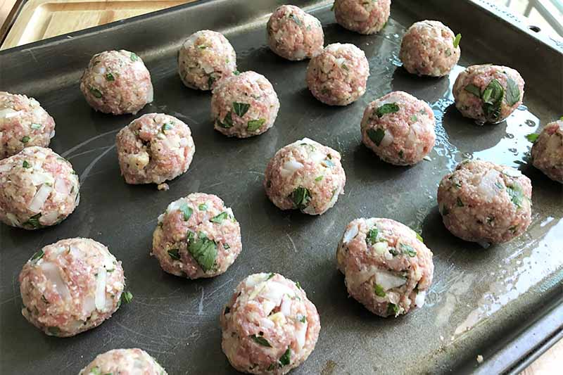 Horizontal image of uncooked round mounds of seasoned beef on a dark baking tray.