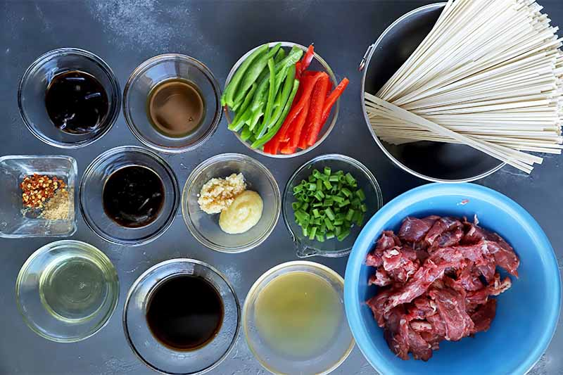 Horizontal image of small glass bowls filled with seasonings and sarges, a bowl of sliced peppers, a bowl of uncooked noodles, and a blue bowl with raw beef.
