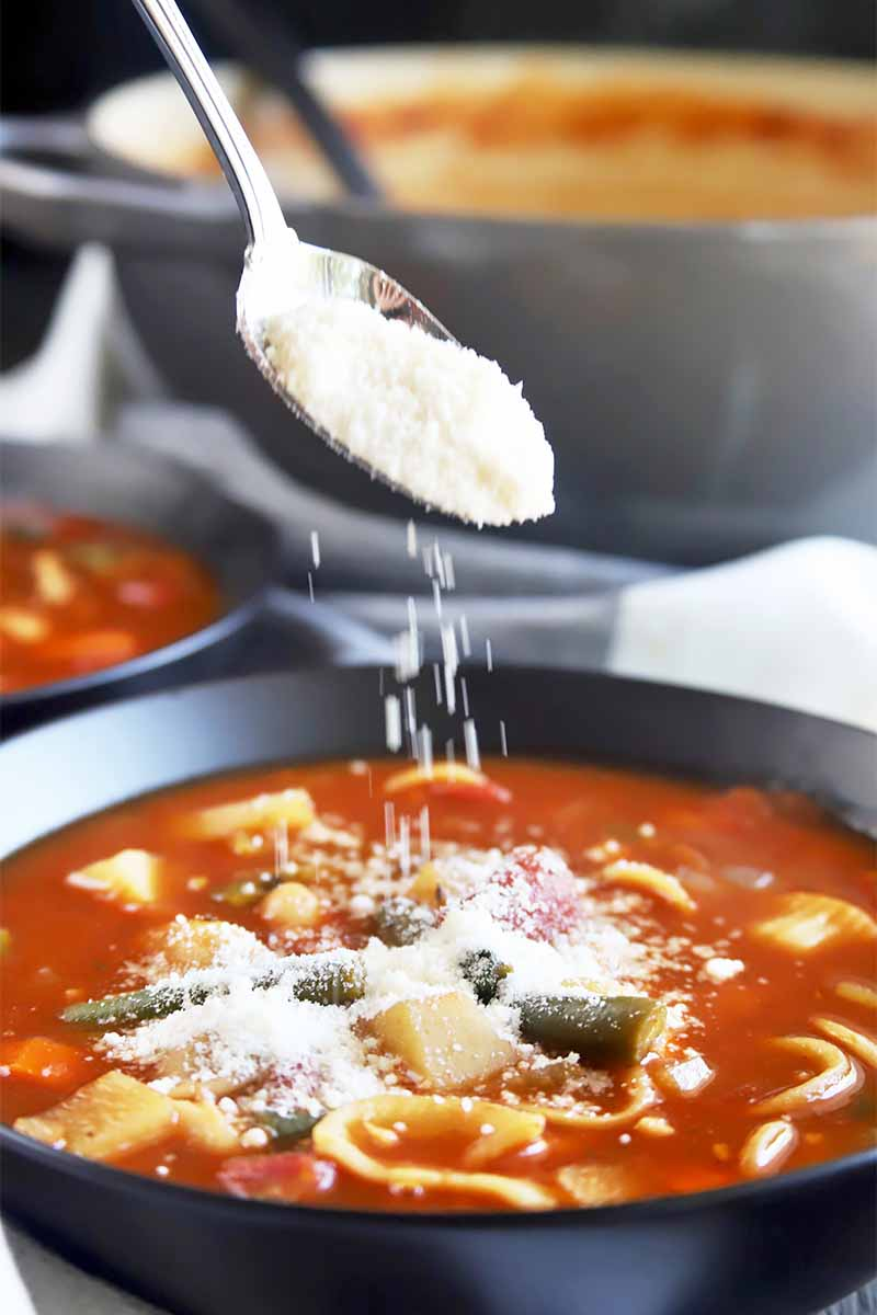 Vertical image of a spoon pouring grated parmesan cheese over a black bowl filled with a tomato and vegetable stew.
