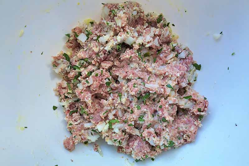 Horizontal image of a mashed beef mixture with onion and herbs in a white bowl.