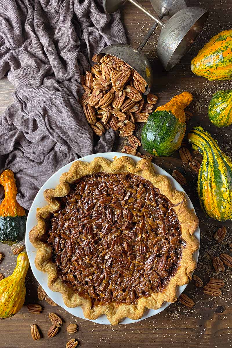 Vertical top-down image of a whole pecan pie in a white plate next to cups of nuts, squash, and a brown towel.