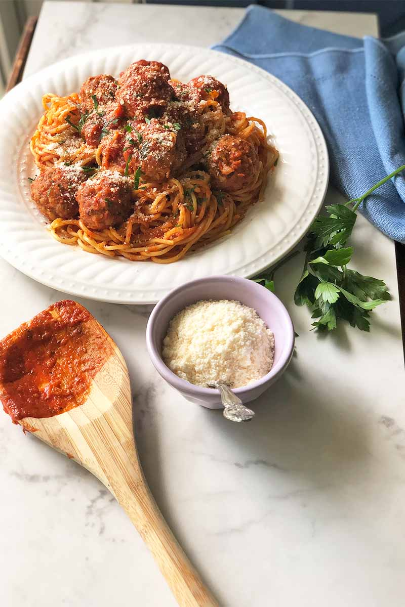 Vertical image of a wooden spoon covered in tomato sauce, a bowl of grated cheese, fresh herbs, a blue towel, and a plate of pasta and meatballs on a white table.
