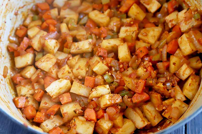 Horizontal image of chopped vegetables cooking in a large pot.