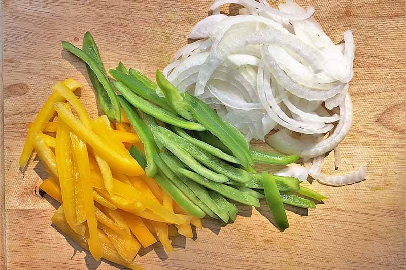 Horizontal image of sliced yellow and green peppers and onions on a wooden cutting board.