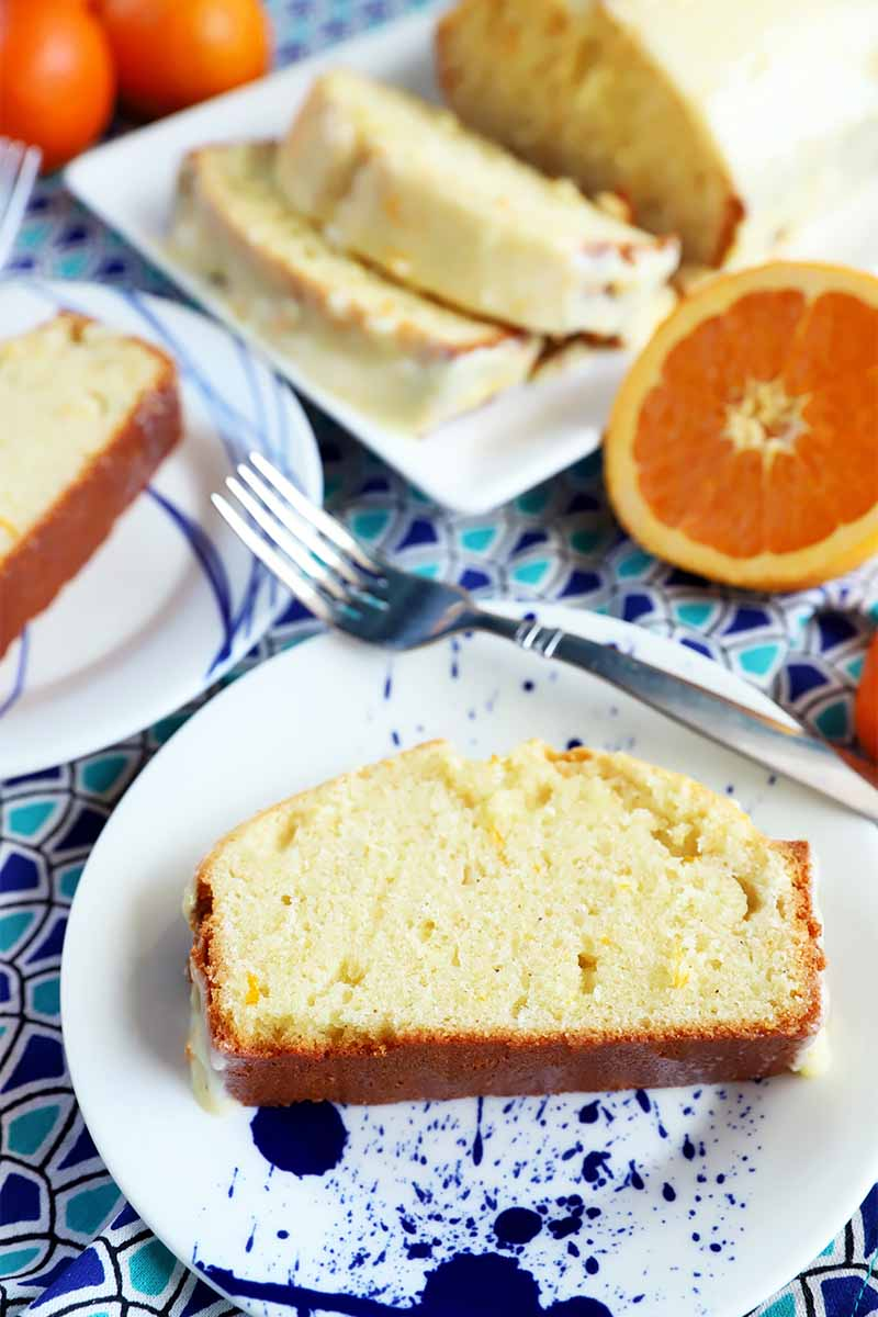 Vertical image of two round plates and one rectangular plate with slices of pound cake on a blue patterned napkin next to metal forks and whole citrus.