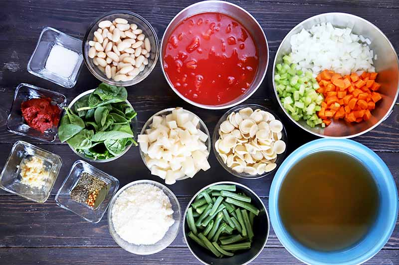 Horizontal image of many bowls of assorted prepped vegetables and seasonings for a vegetarian stew.