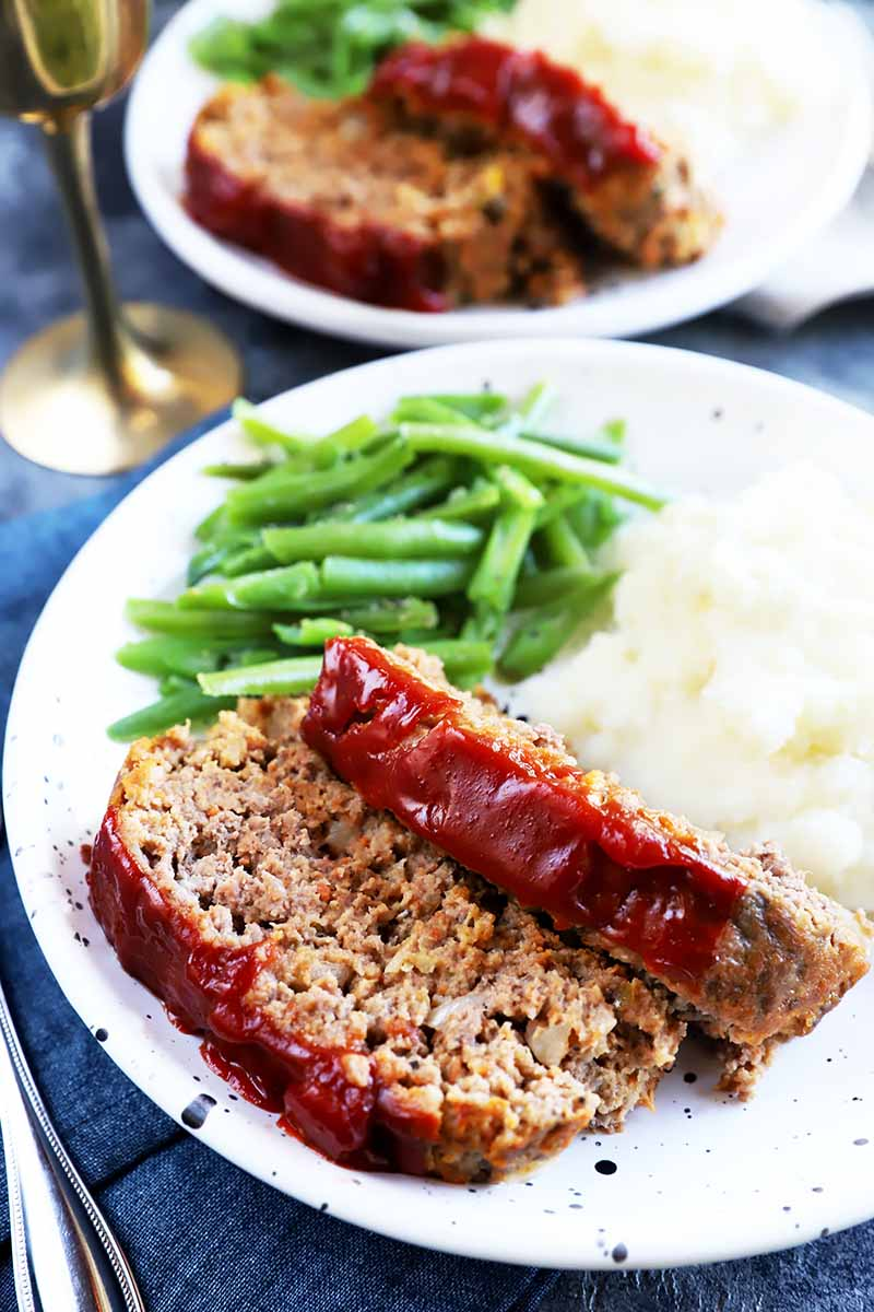 Vertical image of two slices of a meatloaf covered in a ketchup glaze on a plate with mashed potatoes and green beans.