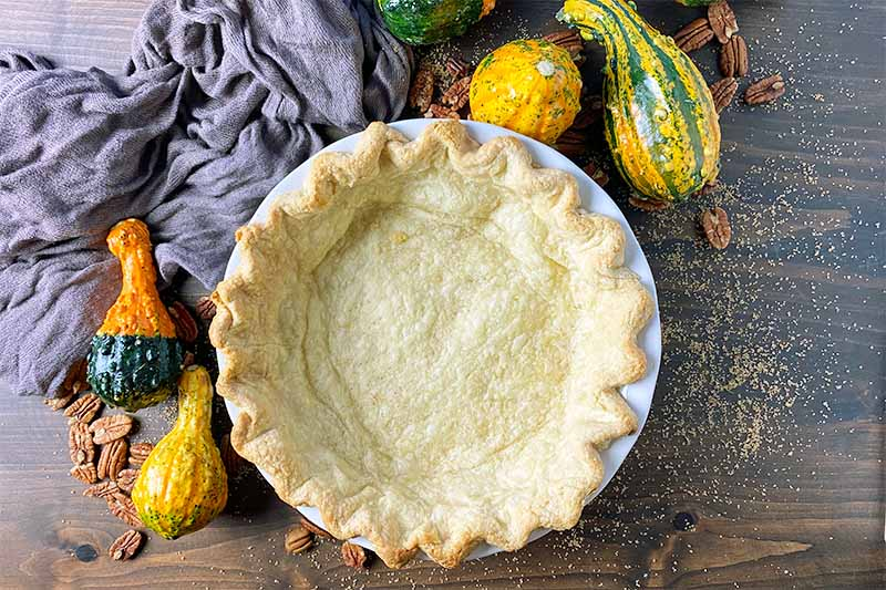 Horizontal image of a partially baked empty pie crust on a wooden table next to squash, sugar, and a brown towel.