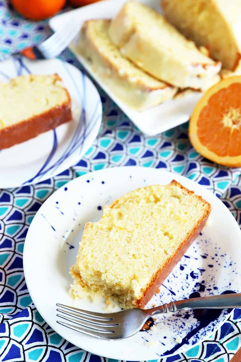 Vertical image of two round plates and one rectangular plate with slices of pound cake on a blue patterned napkin next to metal forks and sliced citrus fruit.